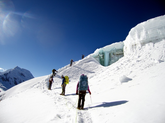The team climes up around a beautiful open crevasse, on hard glacial ice.